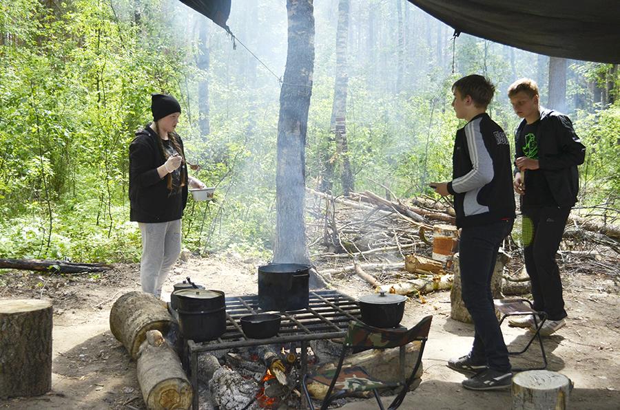 У костра Маша - главный повар лагеря.